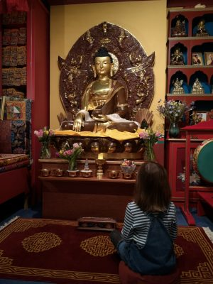 Child sitting in front of Buddha